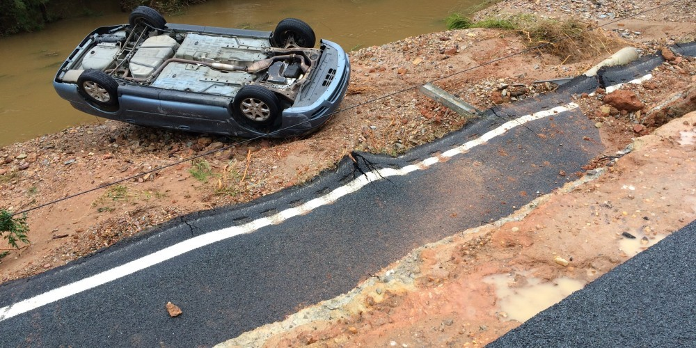 Road collapse in Lugoff, SC on October 5, 2015. The blue vehicle in the background is where the woman was rescued last night and the male DOT was recovered this morning.